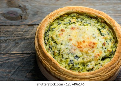 Homemade puff pastry quiche lorraine with leeks swiss gruyere and soft goat cheese with scrumptious golden crust on serving board. Weathered plank barn wood background close up. Copy space.Easter