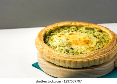 Homemade puff pastry quiche lorraine with leeks swiss gruyere and soft goat cheese with scrumptious golden crust on serving board blue napkin. White kitchen table grey wall. Copy space.Easter