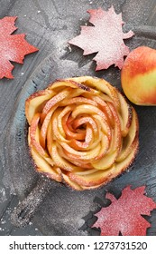Homemade puff pastry with rose shaped apple slices baked in iron skillet. Top lay on wooden board with some apples and sugar
