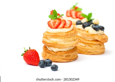 homemade puff pastry stuffed with cream and berries on white