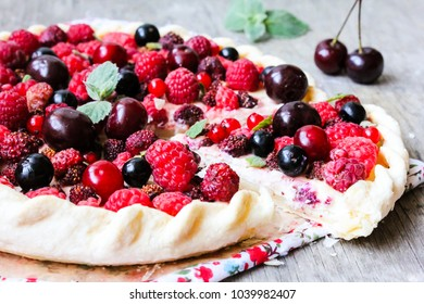 Homemade puff pastry sweet pizza pie with mascarpone cheese cream, fresh ripe raspberry, cherry, black currant and strawberry on a wooden table, selective focus. Summer food. Easter food. Picnic.