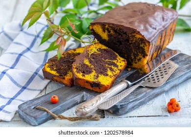 Homemade pumpkin chocolate cake, knife and cake spatula on wooden serving board, selective focus.