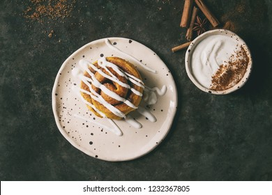Homemade pumpkin cinnamon bun rolls sweet autumn baked dessert with cream cheese sauce in spotted ceramic plates with cinnamon sticks over old dark metal background. Flat lay, space