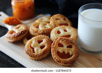 Homemade pumpkin Jam cookie for Halloween with funny faces. Snack with milk.