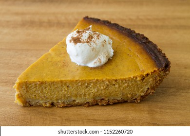 Homemade pumpkin pie on rustic wooden cutting board. Conceptual image for Autumn.
