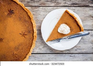 Homemade pumpkin pie on wooden rustic background top view