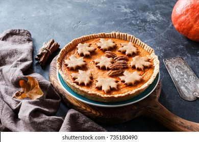 Homemade Pumpkin Pie for Thanksgiving table dinner menu on a wooden cutting board. Side view, selective focus