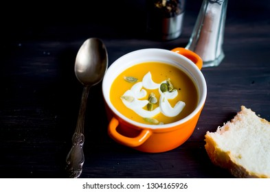Homemade pumpkin soup in ceramic bowl with seeds, sour cream and bread croutons on dark rustic wooden background