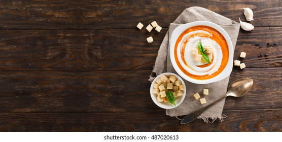 Homemade pumpkin soup with cream, croutons and basil. Old rustic wooden background, top view, flat lay style. Autumn concept. Long web format