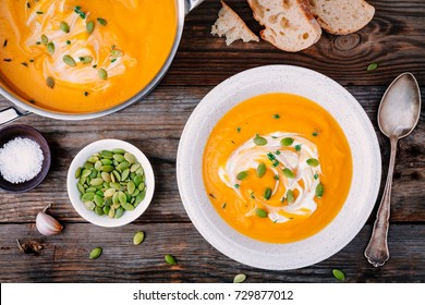 Homemade pumpkin soup with cream and seeds on wooden background