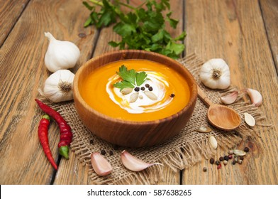 Homemade pumpkin soup with cream with spices on rustic wooden background