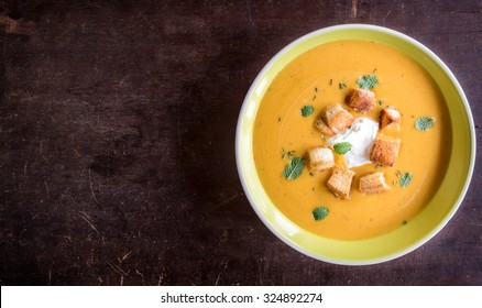 Homemade pumpkin soup with milk cream and croutons bread in plate on wooden background with blank space