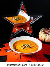 Homemade pumpkin soup on a autumn setting with a mirror star decor