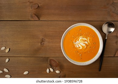 Homemade pumpkin soup in a white plate with cream and seeds flat lay on brown wooden rustic background with copy space