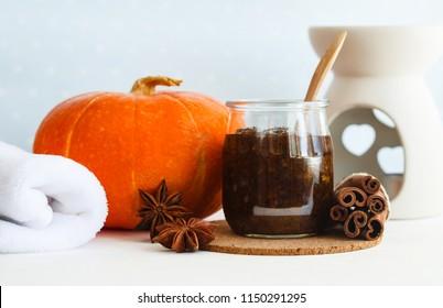 Homemade pumpkin spice facial mask/scrub made with ripe pumpkin puree, sugar and honey, cinnamon powder and ground coffee. DIY cosmetics. Copy space.