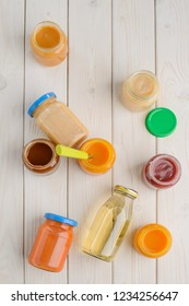 Homemade purees and juices on wooden table. Different flavors of baby food, packaged in glass jars.