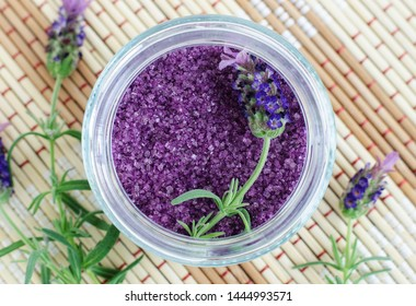 Homemade purple exfoliating scrub (foot soak, bath salt) with essential lavender oil. Lavender flower in the jar. Natural skin and hair care. DIY beauty treatments, spa recipe. Top view, copy space.
