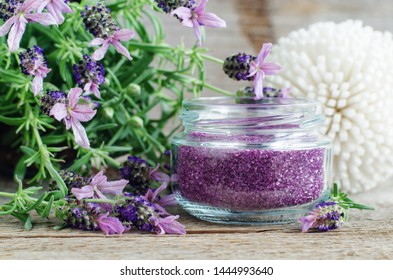 Homemade purple exfoliating scrub (foot soak or bath salt) with essential lavender oil. Topped lavender flowers close up. Natural skin and hair care. DIY beauty treatments, spa recipe. Copy space.