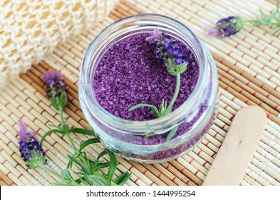 Homemade purple exfoliating scrub (foot soak, bath salt) with essential lavender oil. Topped lavender flower in the jar. Natural skin and hair care. DIY beauty treatments and spa recipe. Copy space.
