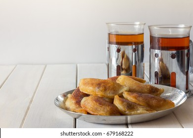 Homemade Qatayef served with Tea on White Wooden Background