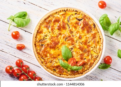 Homemade quiche lorraine with chicken, mushrooms and cheese on white wooden background. French cuisine