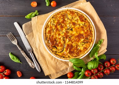 Homemade quiche lorraine with chicken, mushrooms and cheese on black wooden background. French cuisine