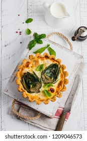 Homemade quiche tart with with artichoke on light wooden background. Vintage style. Top view.