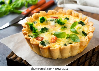 Homemade quiche tart with red fish salmon, broccoli, basil, seasonings and cheese on a gray stone background. Selective focus.