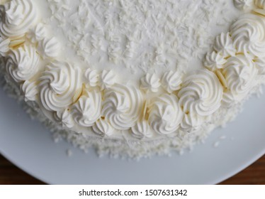Homemade Raffaello cake (coconut almond cake) in a closeup. Decorated with white whipped cream, coconut and almond slices. Beautiful, detailed pastry item. Photographed on a brown wooden surface.