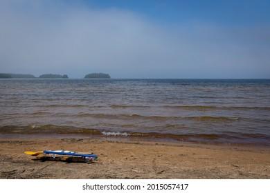 A homemade raft on a beach with a foggy background.