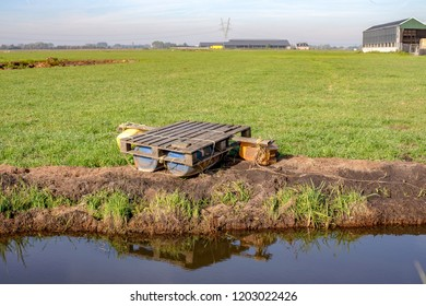 Homemade raft with plastic floaters, pallet and rope, reflection in a creek and a farm at the horizon, on the edge of a meadow.