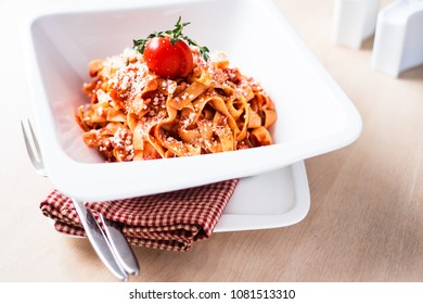 Homemade ragout bolognese with pasta taglietelle. Bolognese sauce is made with minced pork and beef meat, carrot, celery. Traditional italian meal is served with freshly grated cheese in a white bowl.