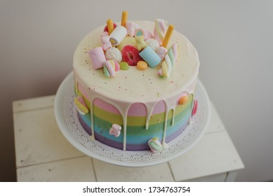 Homemade rainbow cake with candy on top