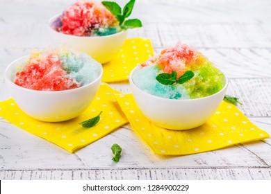 Homemade rainbow shaved ice on white background