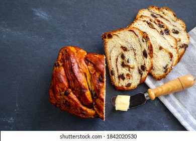 Homemade raisin and cinnamon bread on a gray slate slab with a linen cloth and pat of butter on a knife