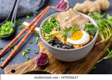 Homemade ramen noodles with meat, egg and green onions in a bowl on a textured gray background, selective focus