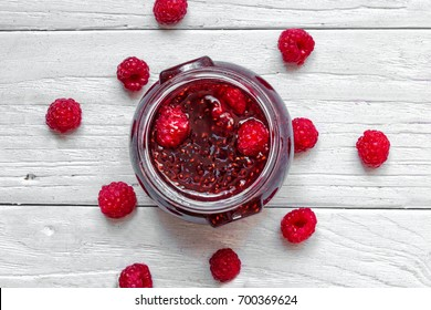 homemade raspberry jam with fresh raspberries on white wooden table. top view