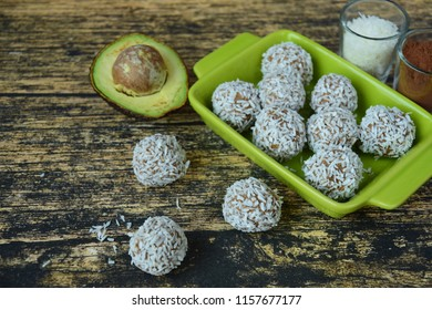 Homemade raw avocado chocolate truffles with nuts, seeds and coconut flakes on wooden background