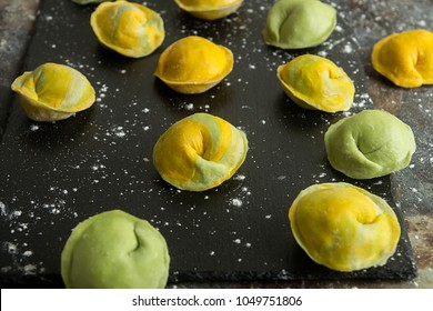 Homemade raw dumpling, yellow and green colors, traditional East European food before boiling. Top view.