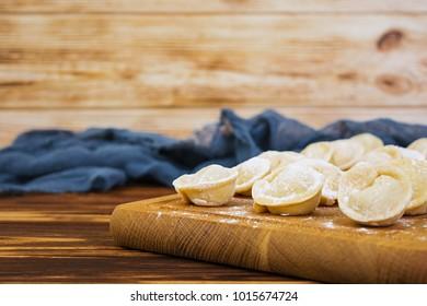Homemade raw dumplings, pelmeni, on wooden background.