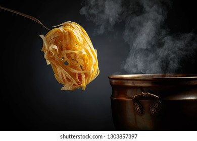 Homemade raw egg noodles and old brass pan with hot water. Black background. Copy space for your text.