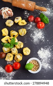 Homemade raw Italian tortellini and basil leaves on a black background, top view