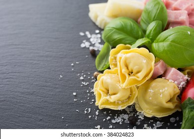Homemade raw Italian tortellini filled with ham and cheese with raw tomatoes, basil leaves and cheese on black background. Healthy food concept with copy space concept. Selective focus.