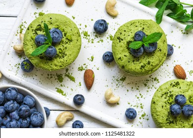 homemade raw matcha powder cakes with fresh berries, mint, nuts. healthy vegan food concept. top view