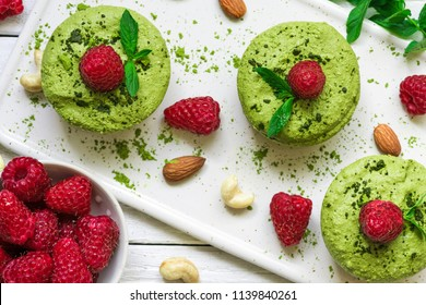 homemade raw matcha powder cakes with fresh raspberries, mint, nuts. healthy vegan food concept. top view