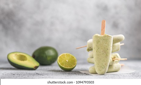 Homemade raw vegan avocado lime popsicle. Sugar-free, non-dairy green ice cream on gray cement textured background. Copy space. Ideas and recipes for healthy snack, dessert or smoothie. Banner