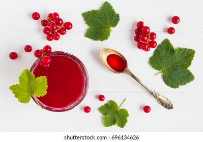 Homemade red currant jelly in a glass jar, green leaves and fresh berries on a white wooden table, top view.