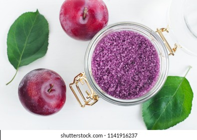 Homemade red plum face and body scrub/foot soak/bath salt in a glass jar. DIY cosmetics for natural skin care. Top view, copy space.