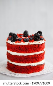 homemade red velvet cake decorated with berries on a light wooden background