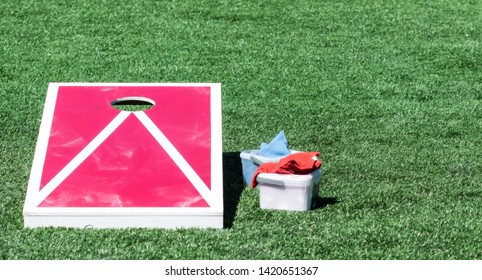 A homemade red and white corn hole board on a green turf field with bean bags in a plastic container next to it.